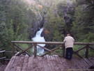 An image of a woman looking at the waterfall of the Siete Tasas (Radal), Chile.